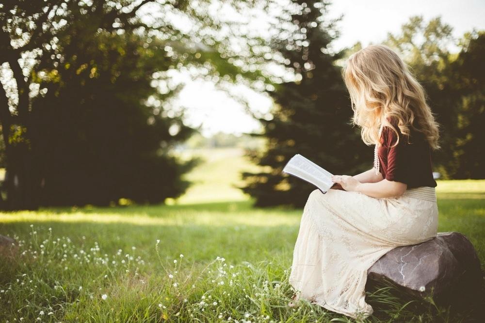Frau auf Wiese mit Buch