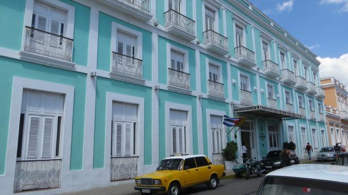 Ein gelbes Taxi vor einem türkisfarbenen Haus in Cienfuegos auf Kuba